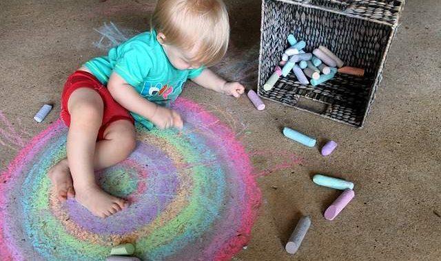 Bambino colora con gessetti